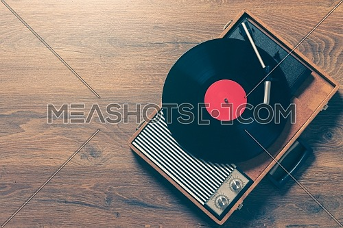 Retro Gramophone with a vinyl record on wooden table, top view and copy space,vintage style with split toning.