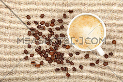 One full white cup of latte cappuccino and roasted coffee beans on background of linen canvas