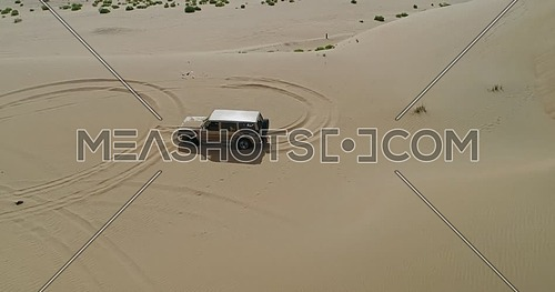 A car moving through sand dunes in the desert