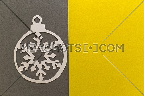 Postcard with paper cut Christmas ball on grey yellow background. Demonstrating trendy color of the year 2021. Illuminating yellow and ultimate gray