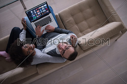 Young multiethnic couple relaxes in the luxury living room, using a laptop computer top view