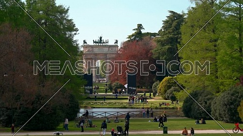"""Milan,Italy- April 13 2021: Parco Sempione (Sempione park) in Milan with Tourists,background view on """" Arco della Pace"""" ( Arch of Peace), Milan,Italy."""