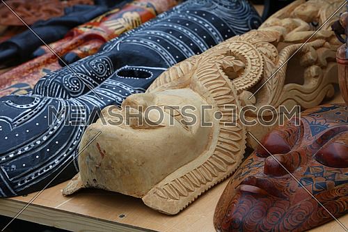Close up Indian and African handmade ethnic wooden carved masks on retail market display, low angle view