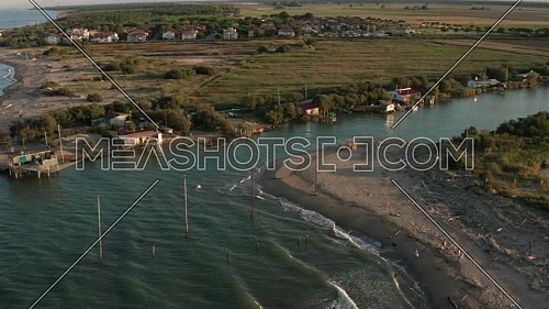 Aerial shot of the valleys near Ravenna (Fiumi Uniti) where the river flows into the sea with the typical fishermen's huts.