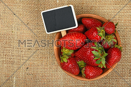 Fresh mellow red strawberries in rustic ceramic bowl with chalk blackboard price tag sign on jute burlap canvas background, top view