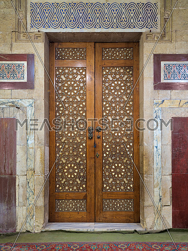 Old aged wooden closed door decorated with arabesque ornaments, al Refai Mosque, Old Cairo, Egypt