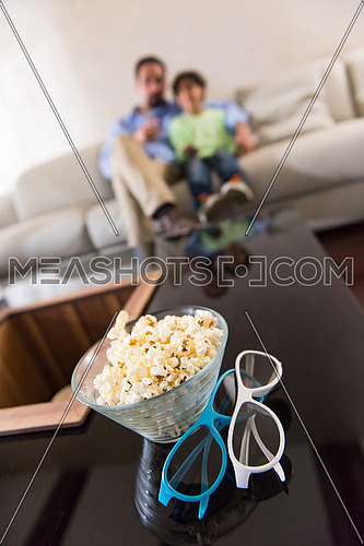 popcorn and 3d glasses on table in livingroom with father and son