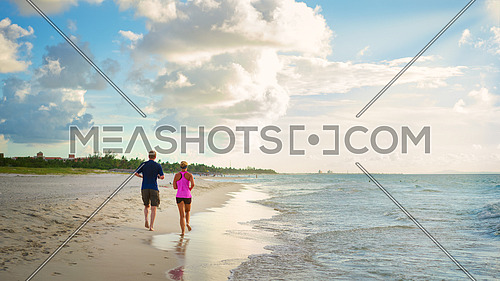 Man and women running on tropical beach at sunset.