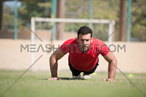 young middle eastern man athlete enjoys doing push-ups outside on a sunny day