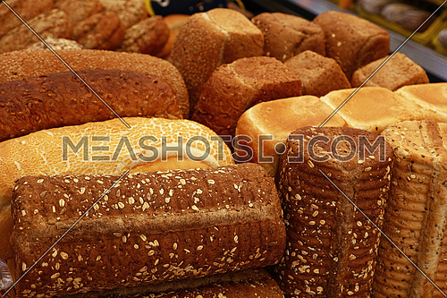 Close up selection of assorted fresh bread loaves on retail display of bakery store, high angle view