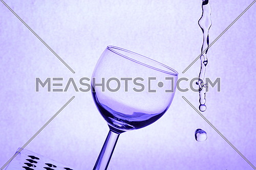 A glass placed in an abstract environment with liquid water poured
