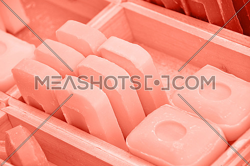 Close up coral pink toned traditional beauty toilet hard soap bars in wooden box on retail display, high angle view