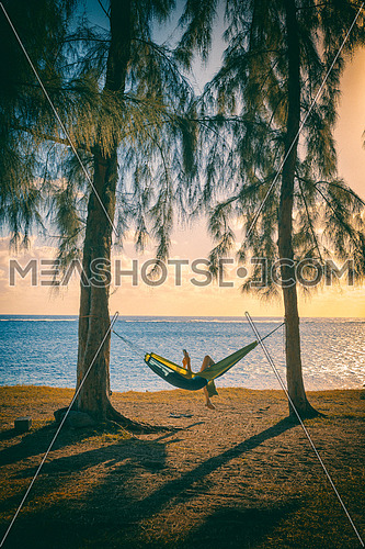 Silhouette of woman reading tablet in hammock,used split toning effect,vertical photo.
