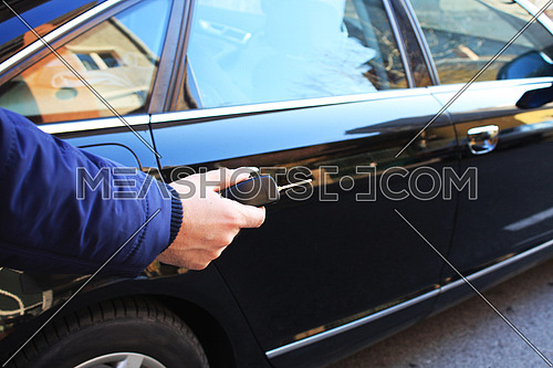 Young man opening car with a key.