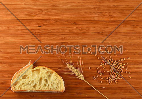 Wooden bamboo cutting board with one wheat ear, handful of ripe grains and a slice of bread - add your text