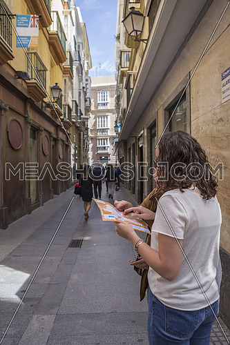 Cadiz, SPAIN -  April 1: Lost tourists look at map of the city in the typical and narrow streets of Cadiz, Andalusia, Spain