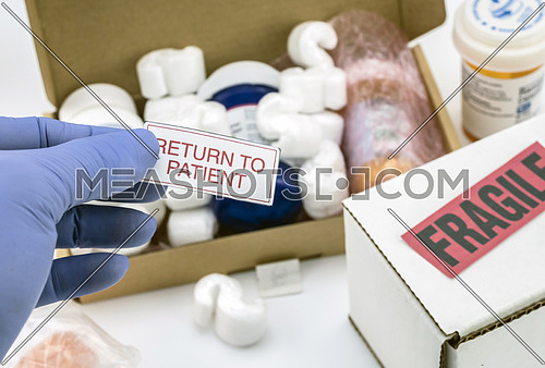 Nurse unpacking medication in boxes, pasting label return to the patient, conceptual image
