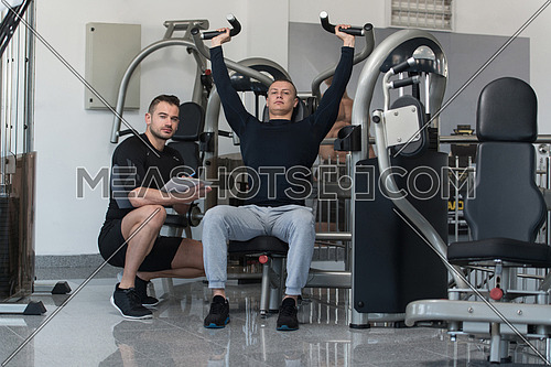 Personal Trainer Showing Young Man How To Train Shoulders On Machine In The Gym
