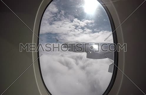 shot from plane window showing wing while flying through clouds