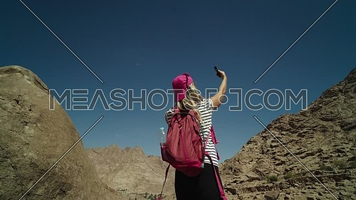 Low angel shot for a female tourist wearing a pink cap and travel backpack taking a selfie at Sinai Mountain for wadi Freij at day.