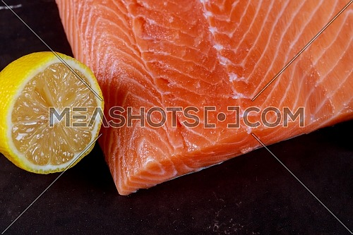Salmon fresh and lemon in black wooden background top view