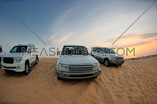 Desert Safari - Off-road jeep vehicles driving in the Arabian Desert at sunset