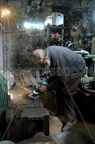 an old black smith woking in his workshop at night