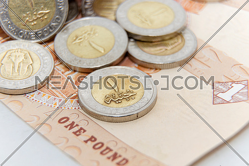 many pieces Egyptian 1 pound gold and silver metal coins dropping on Egyptian pound paper note - banknote  background