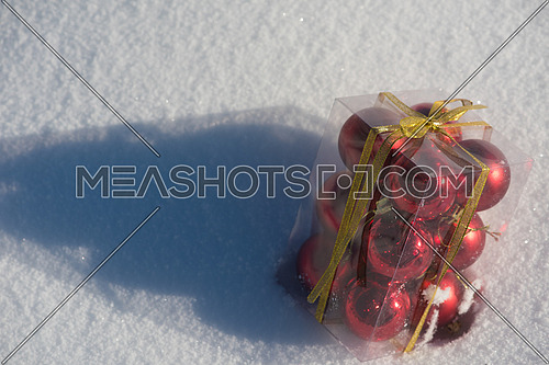 christmas ball in box on fresh  snow at  beautiful sunny winter day