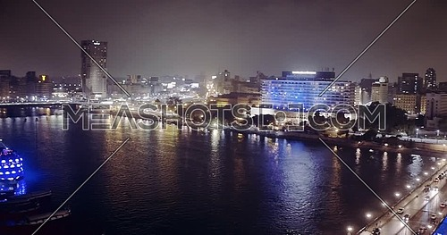 Drone getting down shot to the River Nile revealing The Nile Ritz Carlton Hotel at night