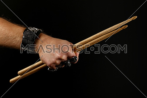 Close up man hand with metal rings and bracelet holding two drumsticks over black background, side view