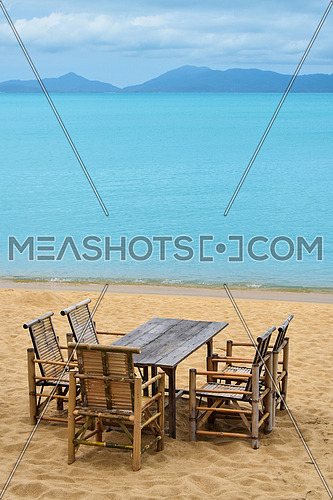 Wooden bamboo furniture, table and five chairs around on sand beach with blue sea water background in Koh Samui island, Thailand