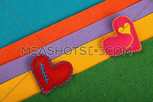 Craft and art, two handmade stitched toy hearts, pink and red on colorful felt diagonal stripes background