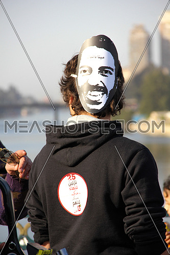 A man from his back wearing mina danial mask in a protest