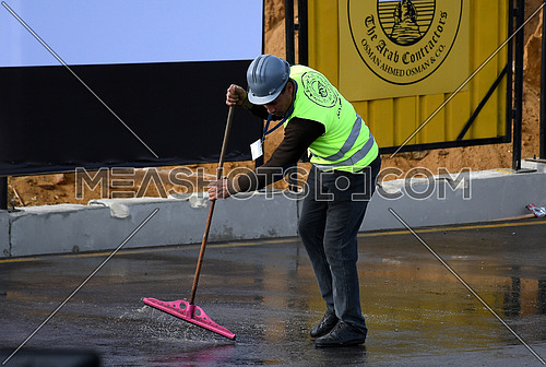 Mid shot for a worker cleaning the ground at the Ramses II Statue transferring to The Grand Egyptian Museum Event in Cairo on 25 January 2018