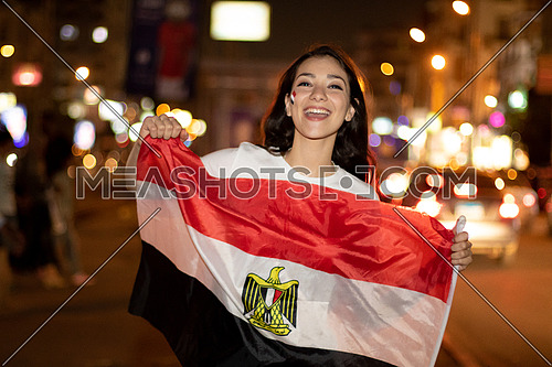 Egyptian football Female supporter in the street holding Egyptian flag dressed in red