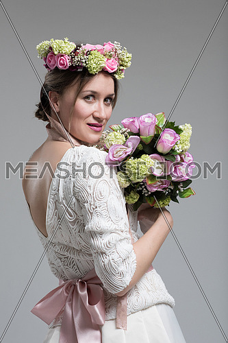 Young attractive bride with the a bouquet of flowers isolated on white background.