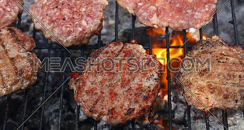 Several beef or pork meat barbecue burgers for hamburger prepared grilled on bbq fire flame grill