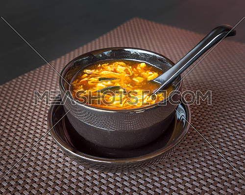 Chinese food, hot and sour soup served in black bowl with spoon on dark background.