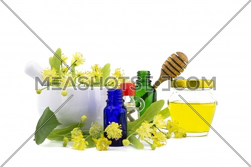 Fresh Linden or Tilia flowers and leaves with bottle of honey and essential oil bottles in a therapeutic still life for alternative healing