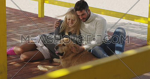 Couple With A Dog enjoying time  together On The Beach at autumn day