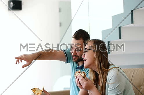 Happy Couple Eating Pizza At Home in Slow motion