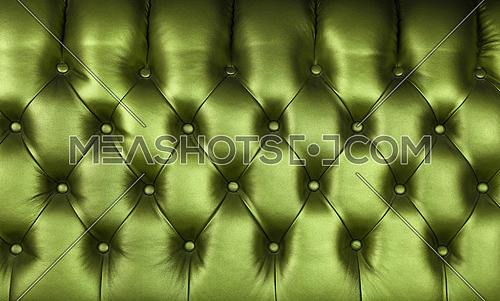 Background texture of dark green capitone genuine leather, retro Chesterfield style soft tufted furniture upholstery with deep diamond pattern and buttons, close up