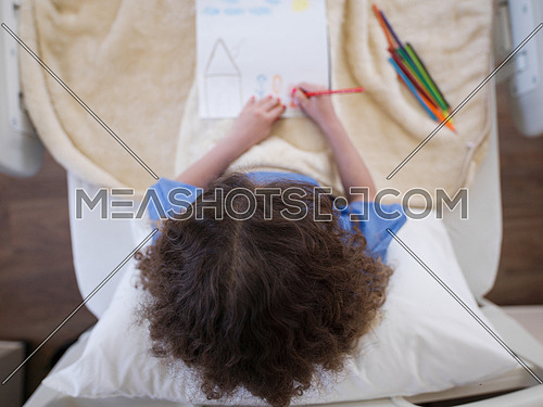 top view of little girl painting home and family at hospital bed