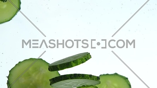 Close up several fresh green cucumber slices thrown and floating in clear transparent water, low angle side view, slow motion