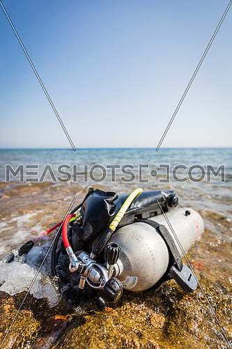 Diving gear laid out on the shore at day
