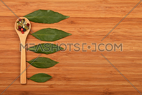Scale of bay laurel leaves and mix of peppercorn in wooden spoon on bamboo wood chopping board background