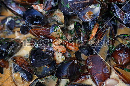 Cooking seafood saute steamed and roasted mussels and shrimps in sauce, close up, elevated high angle view
