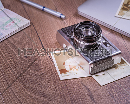 Vintage image with old Camera,old photo,laptop,pen and passport on wood table.