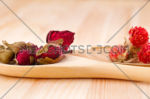 dry floral herbal tea on wood spoon over wooden table